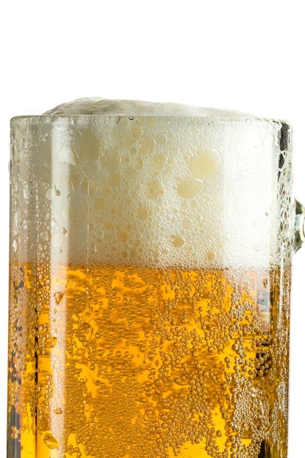 Cerveja clara de derramamento em uma caneca de cerveja, despeja a espuma e o pulverizador fotos de stock