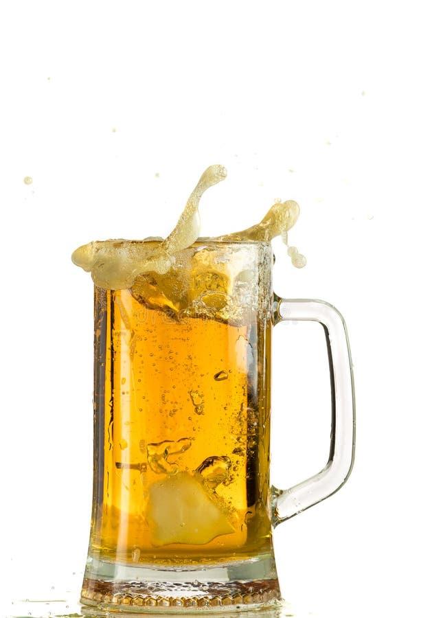 Cerveja clara de derramamento em uma caneca de cerveja, despeja a espuma e o pulverizador foto de stock royalty free