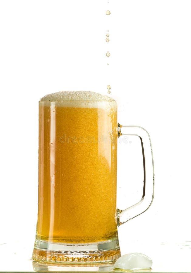 Cerveja clara de derramamento em uma caneca de cerveja, despeja a espuma e o pulverizador fotografia de stock royalty free