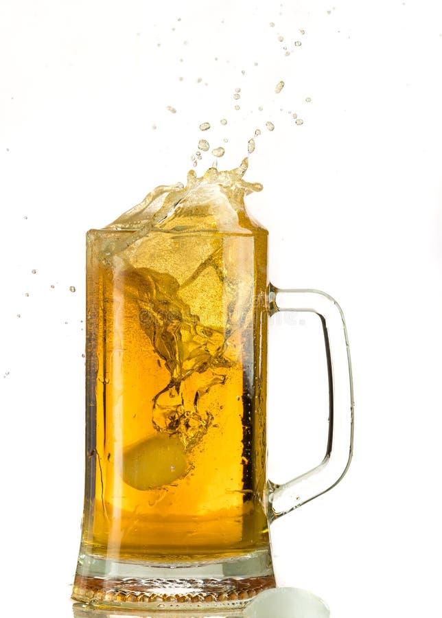 Cerveja clara de derramamento em uma caneca de cerveja, despeja a espuma e o pulverizador foto de stock