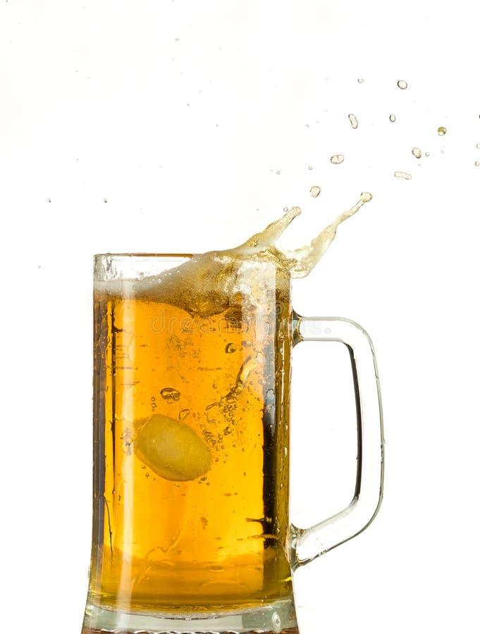 Cerveja clara de derramamento em uma caneca de cerveja, despeja a espuma e o pulverizador imagem de stock royalty free