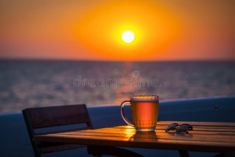 Cerveja com bokeh no mar fotografia de stock