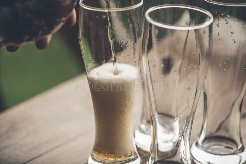 A cerveja com luz da espuma derramou nos vidros que estão em um woode imagens de stock