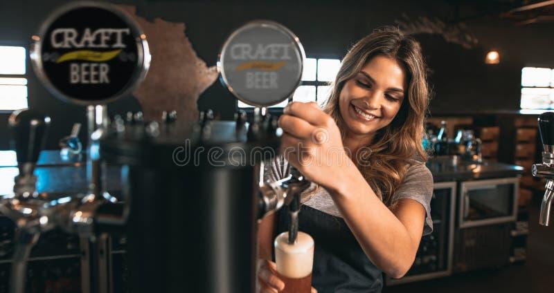 Cerveja de batida do ofício do barman fêmea na barra fotografia de stock