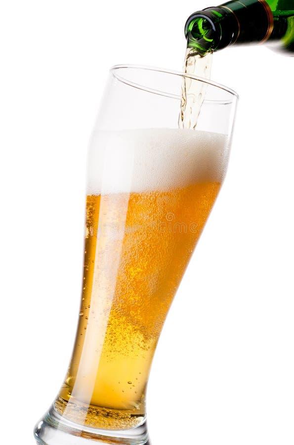 Cerveja de derramamento da garrafa ao vidro no fundo branco imagem de stock royalty free