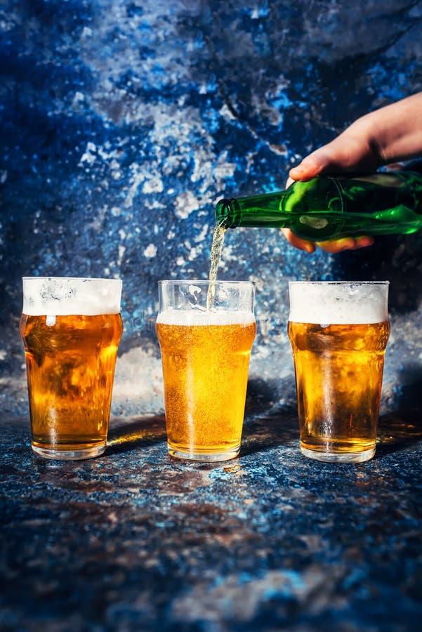 Cerveja de derramamento da mão do empregado de bar da garrafa em vidros de cerveja foto de stock