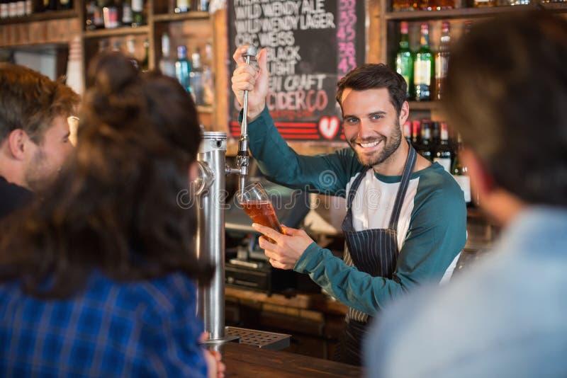 Cerveja de derramamento de sorriso do barman no vidro para clientes imagens de stock