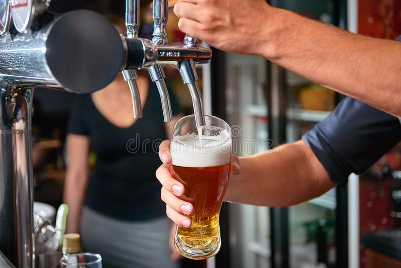 Cerveja de derramamento do barman da torneira atrás da barra Mulher borrada no fundo foto de stock royalty free