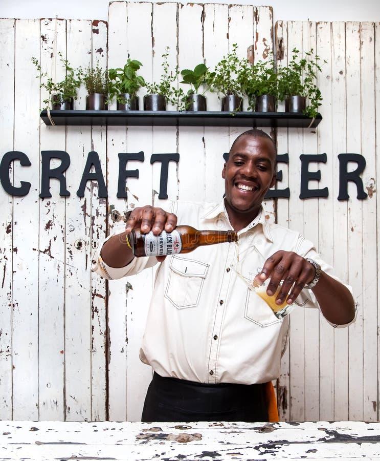 Cerveja de derramamento do empregado de bar no vidro fotografia de stock royalty free