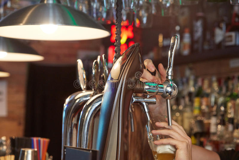 Cerveja de derramamento do empregado de bar imagem de stock royalty free