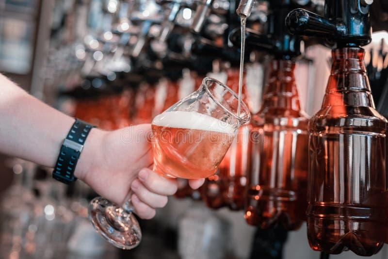 Cerveja de derramamento do ofício do empregado de bar ocupado nos vidros domingo à noite fotos de stock