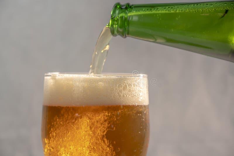 Cerveja de derramamento em um vidro de uma garrafa imagem de stock