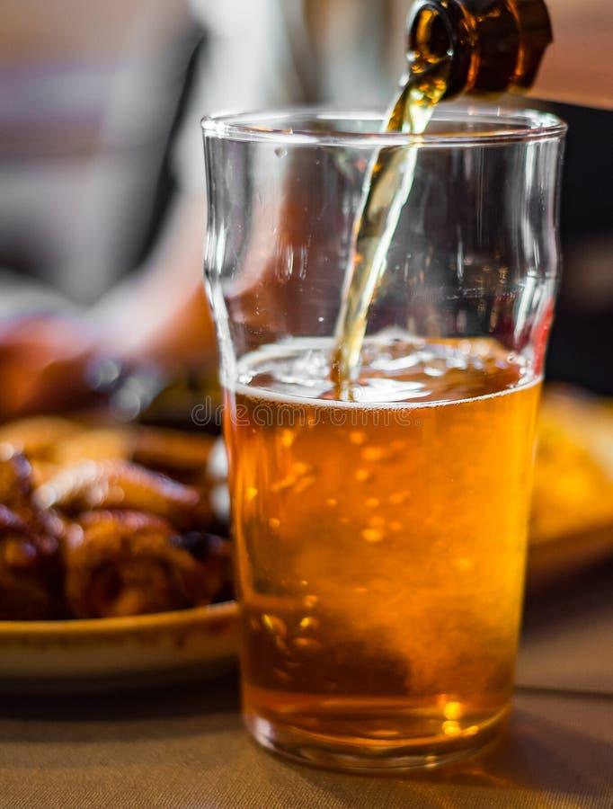 Cerveja de derramamento no vidro da garrafa na barra fotografia de stock royalty free