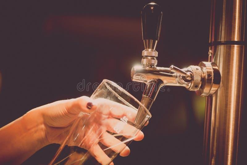 Cerveja de esboço de derramamento em um vidro imagem de stock