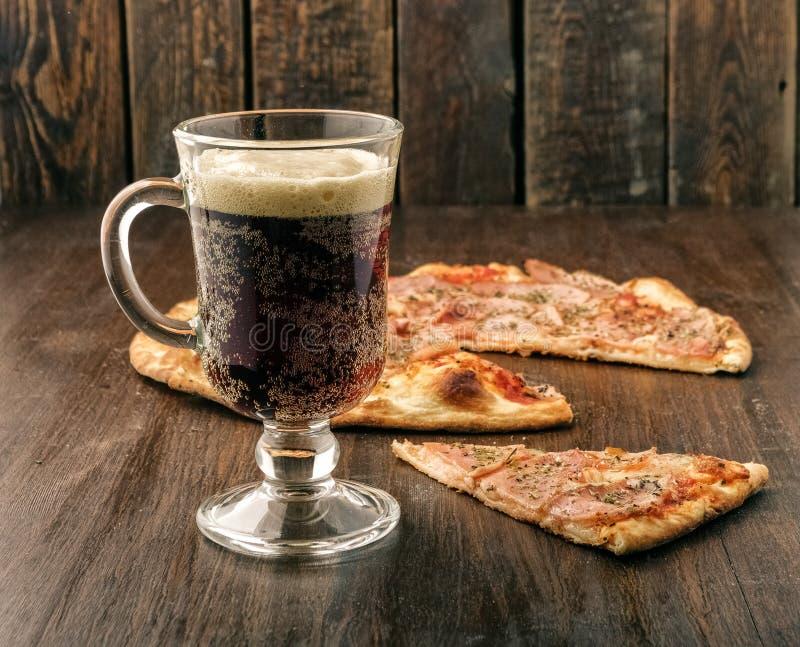 Cerveja de vidro com pizza da fatia no fundo escuro imagens de stock
