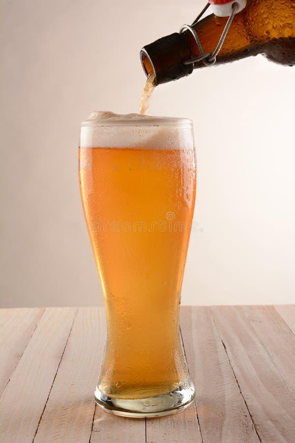 A cerveja derrama a garrafa superior do balanço fotos de stock royalty free