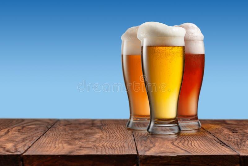 Cerveja diferente nos vidros na tabela de madeira e no fundo azul foto de stock royalty free