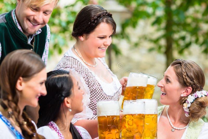 Cerveja do serviço da empregada de mesa no jardim da cerveja imagens de stock