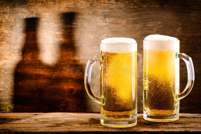Cerveja dois clara fria fresca em uma caneca de cerveja com espuma e gotas de w imagem de stock