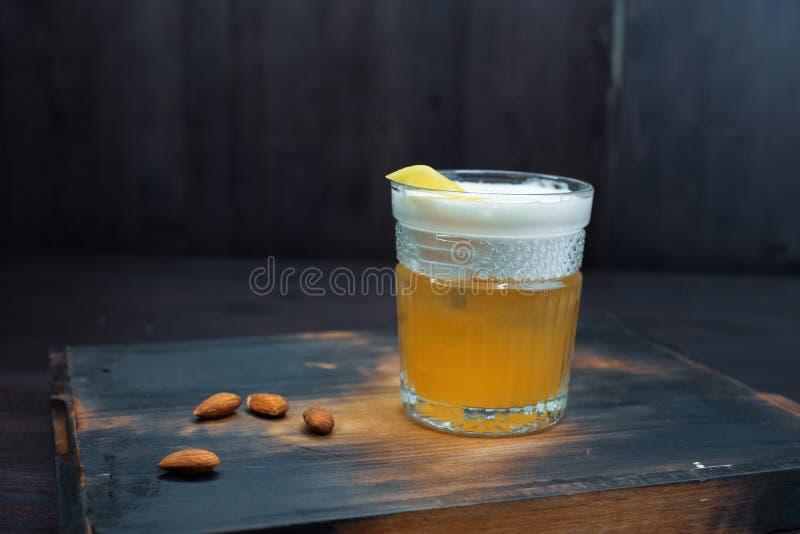A cerveja dourada com espuma branca em um vidro de cerveja está estando em uma tabela de madeira preta na barra A bebida é decora imagens de stock