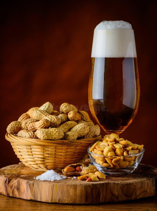 Cerveja e amendoins de vidro fotografia de stock royalty free