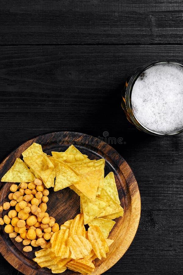 Cerveja e petiscos de cerveja pilsen na tabela de madeira preta Porcas, microplaquetas Vista superior com Copyspace imagem de stock royalty free