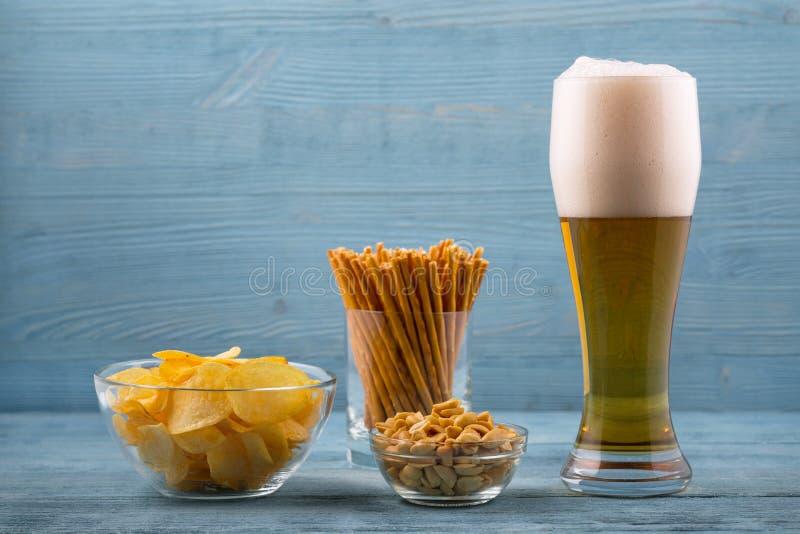 Cerveja e petiscos, microplaquetas, varas de pão e amendoins fotografia de stock