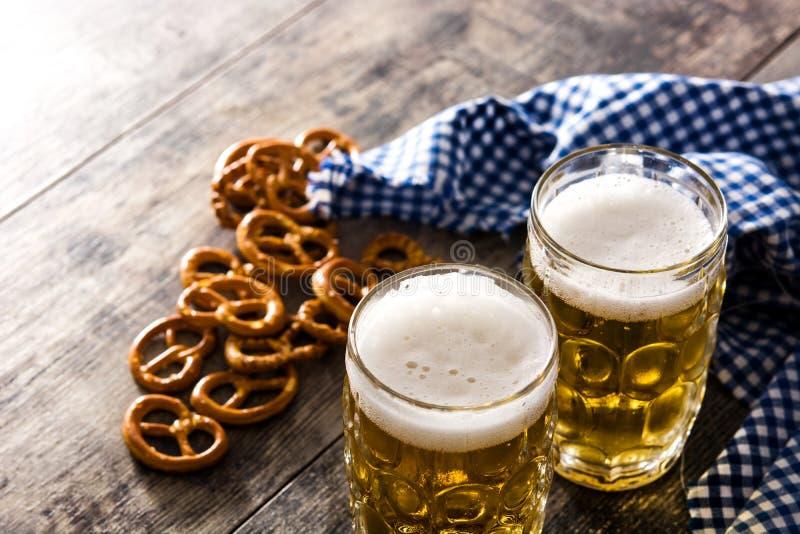 Cerveja e pretzel de Oktoberfest na tabela de madeira fotografia de stock