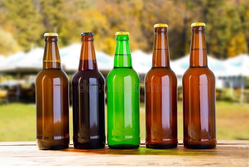 Cerveja em uma tabela de madeira em um fundo borrado de barracas do verão imagens de stock