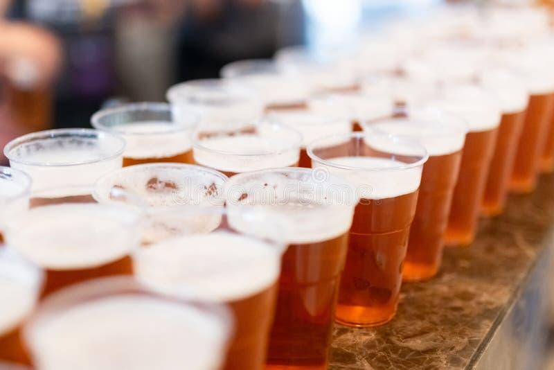Cerveja em vidros bebendo plásticos no contador da barra fotografia de stock