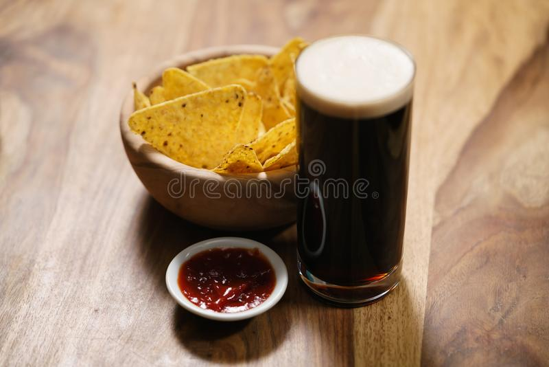Cerveja escura com nachos e molho da salsa foto de stock royalty free