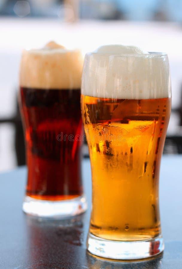 Cerveja escura e clara de vidro fotografia de stock royalty free