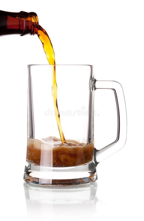 A cerveja está derramando em um vidro do frasco fotos de stock royalty free