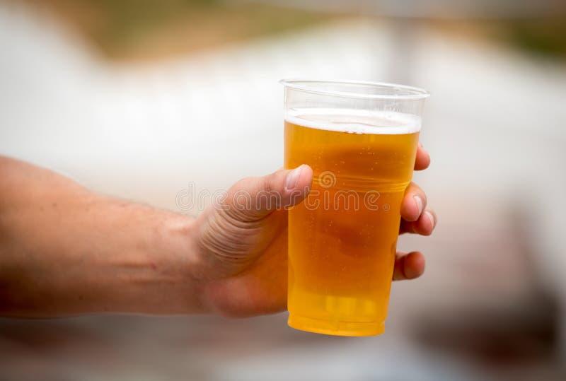 Cerveja fresca em um copo plástico na mão imagem de stock