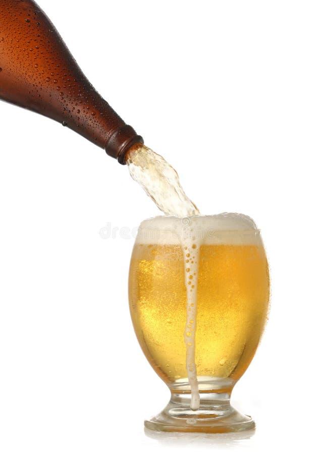 Cerveja fria de derramamento no vidro imagens de stock royalty free