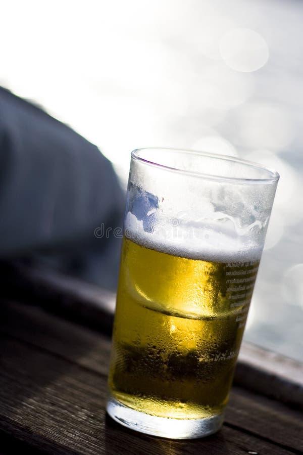 Cerveja fria no peitoril do indicador imagens de stock