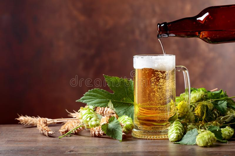 Cerveja, gr?o e l?pulos em uma tabela de madeira velha fotos de stock