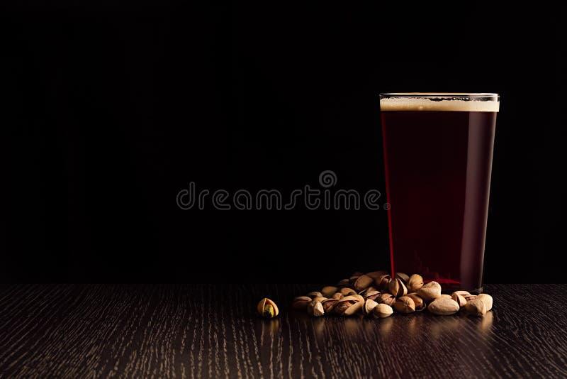 A cerveja inglesa e os petiscos vermelhos da cerveja foto de stock