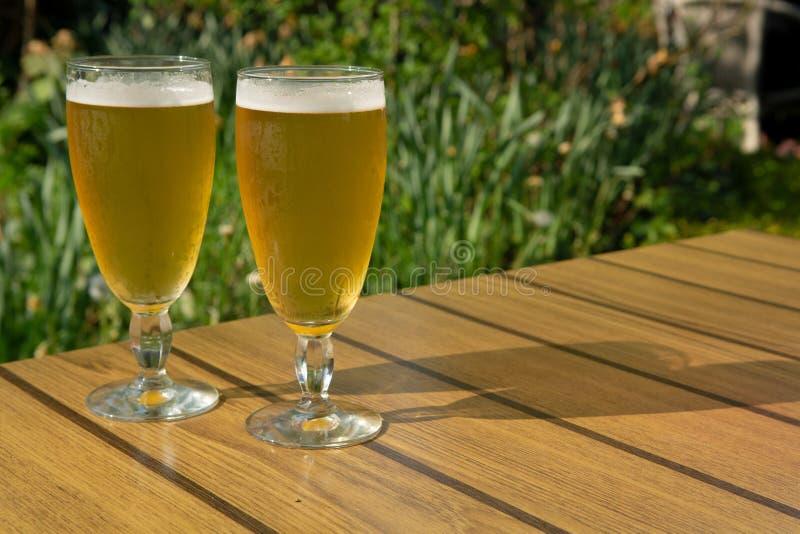 A cerveja não filtrada da luz dois fria nos vidros serviu no outdoo ensolarado imagem de stock