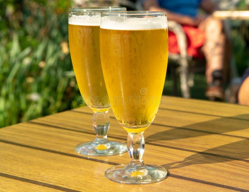 A cerveja não filtrada da luz dois fria nos vidros serviu no terraço exterior ensolarado no jardim imagens de stock royalty free