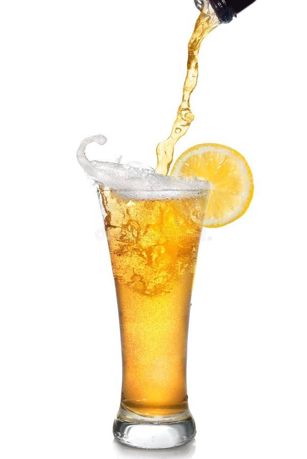 Cerveja que derrama da garrafa no vidro fotos de stock