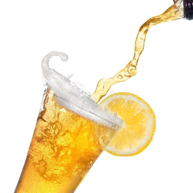 Cerveja que derrama da garrafa no vidro com limão fotos de stock