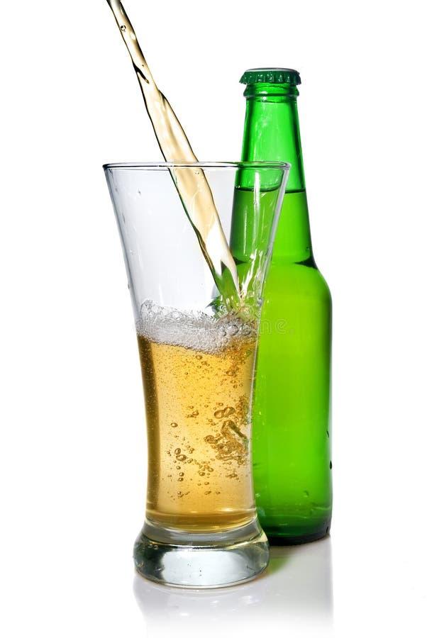 Cerveja que derrama no vidro isolado fotos de stock