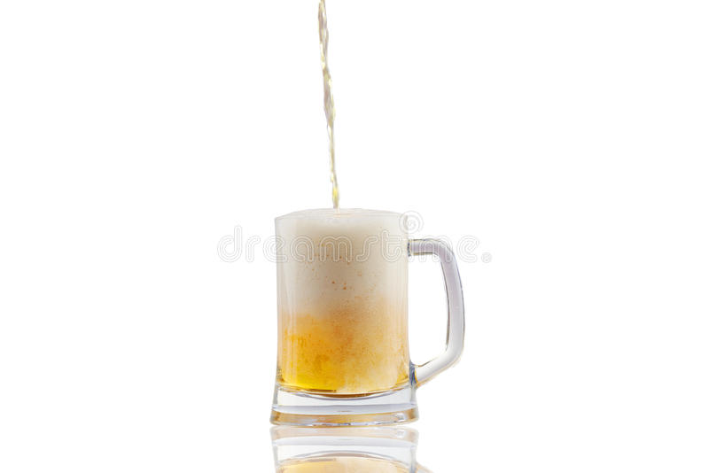 Cerveja que derrama no vidro meio cheio sobre o fundo branco imagens de stock