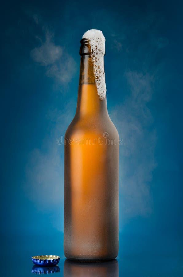 Cerveja que espuma fora da garrafa marrom imagem de stock royalty free