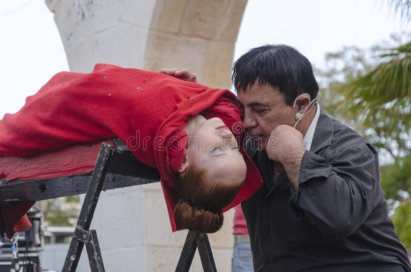 Cerveja-Sheva, ISRAEL - 5 de março de 2015: O mágico executa na sessão da hipnose da cena da rua com a menina no vermelho - Purim fotografia de stock royalty free