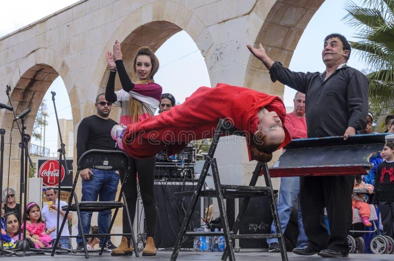 Cerveja-Sheva, ISRAEL - 5 de março de 2015: O mágico executa na sessão da hipnose da cena da rua com a menina no vermelho - Purim fotos de stock