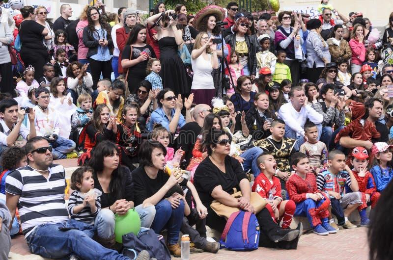 Cerveja-Sheva, ISRAEL - 5 de março de 2015: Os pais com crianças sentam e olham o desempenho na rua - Purim imagens de stock