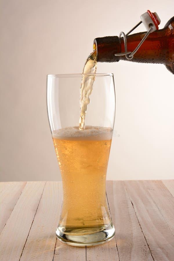A cerveja superior da garrafa do balanço derrama foto de stock