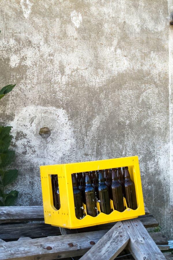 Cerveja vazia escura Bootle na caixa amarela do caso nas partes de madeira na parte externa na frente da parede do cimento fotografia de stock royalty free